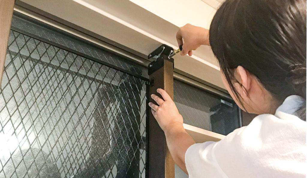 突っぱりジャッキで窓枠に固定しているところ