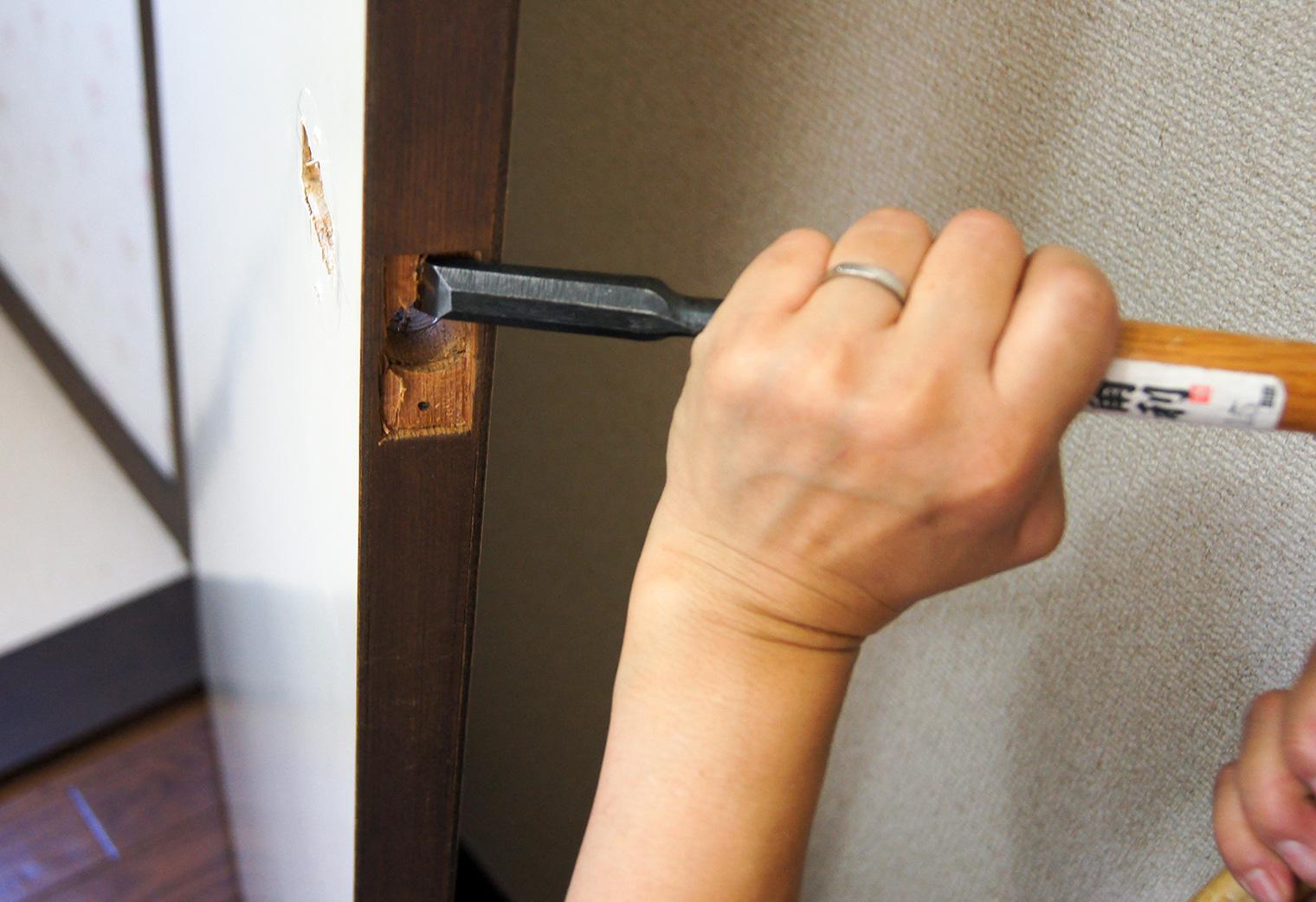 ノミでドアに穴を開ける様子
