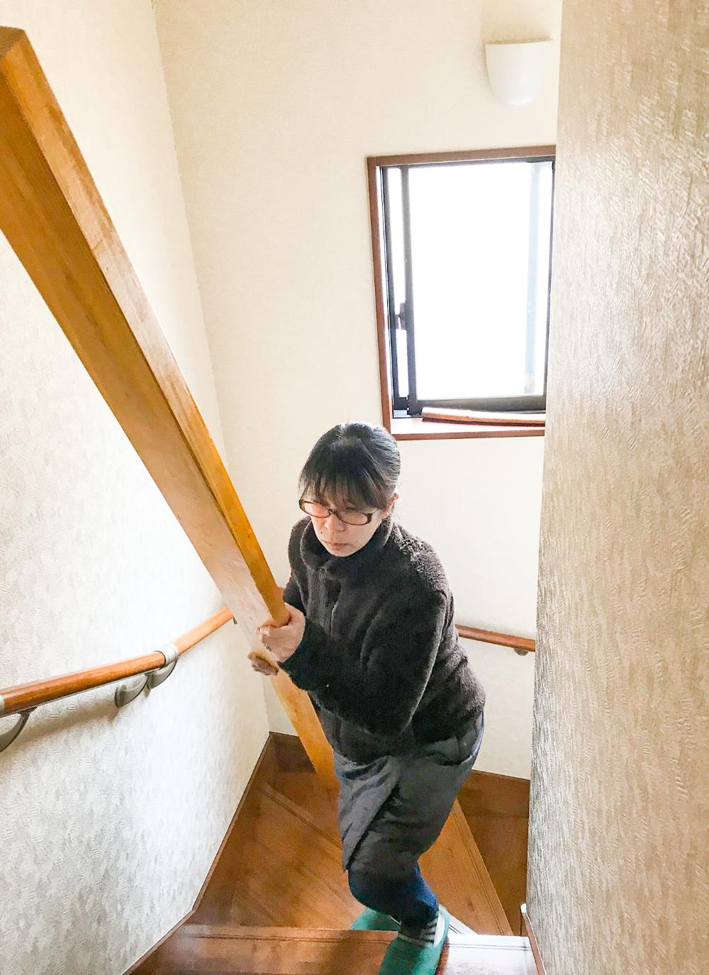 日浅さんの奥さんが木材を持って階段を登る様子